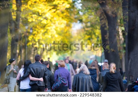 Walking people in the fallen park with orange trees - stock photo