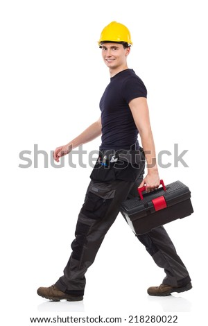 Walking repairman carrying toolbox. Manual worker walking with toolbox and looking at camera. Full length studio shot isolated on white. - stock photo