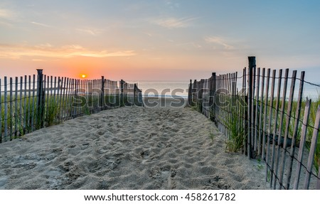 Walking the path to the beach at sunrise over the Atlantic Ocean near Bethany Beach in Delaware.