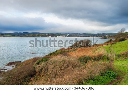 Walking the South West Coast Path as it approaches Polkerris near St Austell on the south coast of Cornwall - stock photo