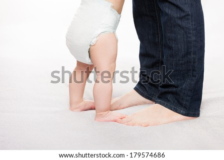 Walking toddler concept - little baby child boy making first step holding mother  - stock photo