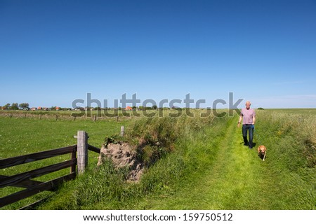 Walking with dog on Dutch wadden island Texel - stock photo