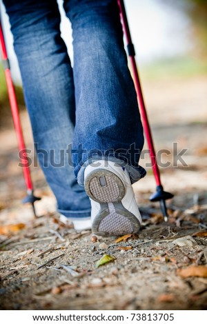 Walking with nordic walking sticks - stock photo