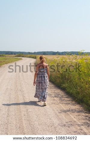 Walking woman on country road.