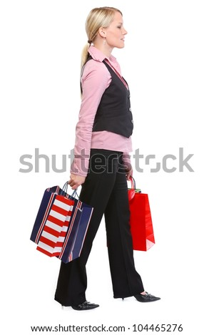 Walking woman with shopping bags. Side view - stock photo