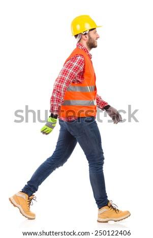 Walking worker in yellow helmet and orange waistcoat. Full length studio shot isolated on white. - stock photo