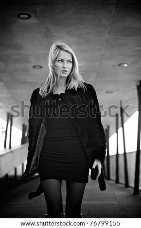 Walking young blonde woman. Black-white photo.