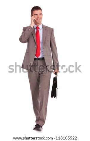 walking young business man with briefcase , looking away from the camera while speaking on his hone, isolated on white background - stock photo