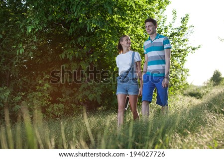 Walking young couple outdoors - stock photo