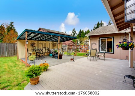 Walkout deck with patio area and wood pergola. Pergola furnished with patio dining table set and sofa. Decorated with flower pots - stock photo