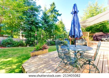 Walkout deck with patio table and umbrella overlooking backyard garden - stock photo