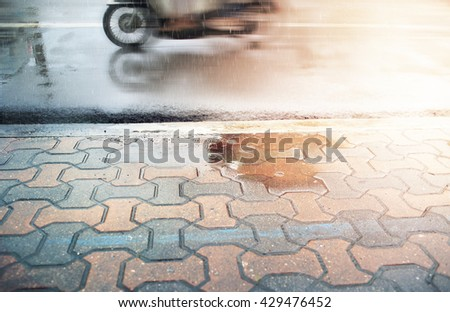 Walkway and wet street during rain fall,selective focus and motion blur. - stock photo