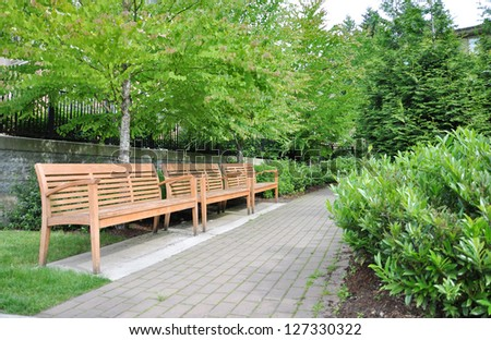 Walkway and wooden chair in the park - stock photo