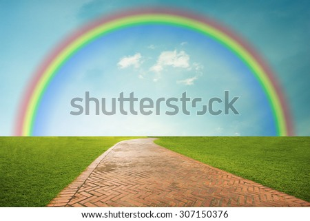 Walkway between green fields and rainbow in blue sky background