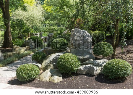 Walkway in the Japanese garden with plants, trees and stones. Horizontally. - stock photo
