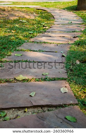 Walkway on green grass field in the park - stock photo