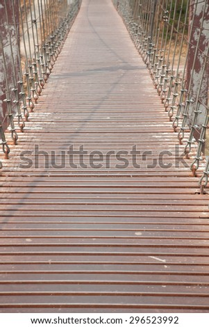 Walkway on the bridge. The metal rod attached to a rope bridge across the river. - stock photo