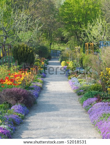 Walkway Through Peaceful Spring Scenery with Blossoms - stock photo