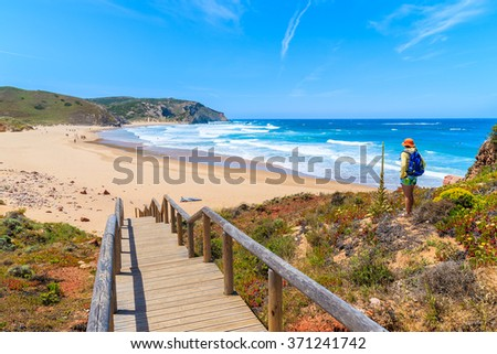 Walkway to Praia do Amado beach and young woman tourist looking at sea, Algarve region, Portugal