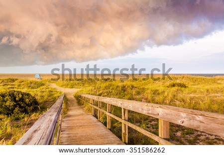 Walkway to the Tybee beach during a cloud golden hour. It is located in the Tybee island, Georgia, Us. - stock photo