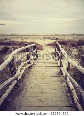 Walkway with driftwood railings leading to beach with driftwood - stock photo