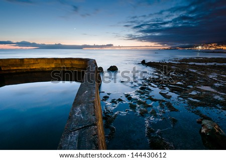 Wall and stones in water at dusk time landscape - stock photo