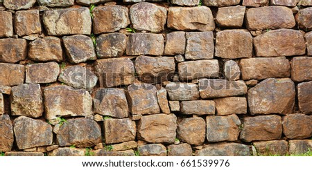 Wall assembled from a roughly processed natural stone. The Background