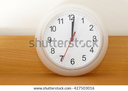 Wall clock on a wood background show the twelve o'clock - stock photo