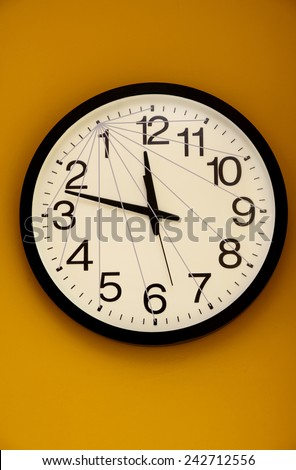 Wall clock with the order of the numbers inverted and a net of lines - stock photo