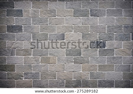 Wall composed of tiles in gray stone - stock photo