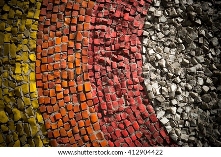 Wall decorated with mosaic tiles and colored bricks Photo executed in dark colors, the edges of a small vignette. A whimsical pattern. It can be used as the background or texture for any photo editor. - stock photo
