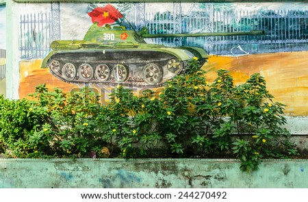 Wall decorated with the Tank and Vietnam National Flag and lot of wild flowers, Saigon, Vietnam - stock photo
