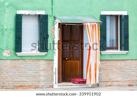 Wall detail with two windows and an open door - stock photo