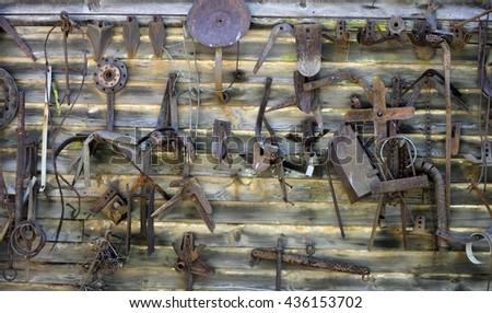 Wall filled with old rusty tools and parts hanging on wall - stock photo