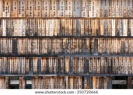 Wall full of weathered wood boards (ema) with the names of the donors and dates at the entrance of the Fushimi Inari Shrine in Kyoto, Japan. - stock photo