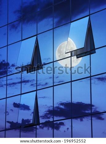 wall glass skyscraper with reflection of the sky and the three open windows at night  - stock photo