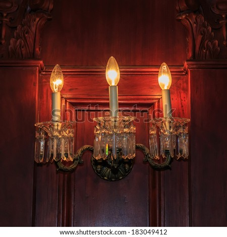 wall light of gilded metal with two electric candles on the wooden wall