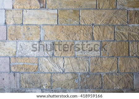 Wall made from sandstone bricks of regular shapes and different color slotting together precisely. Close up architecture photography. Creative wallpaper photography. - stock photo