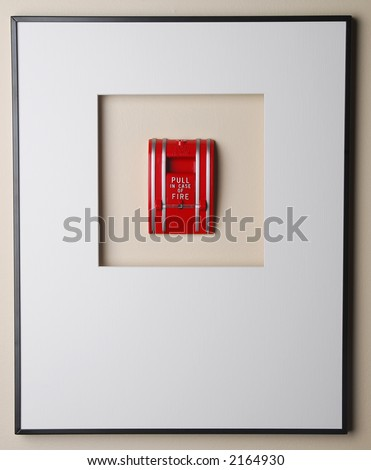 Wall mounted fire alarm surrounded by picture frame. - stock photo
