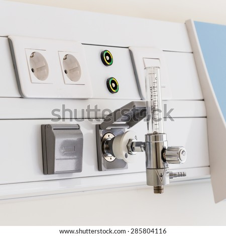 Wall-mounted Thorpe tube, or flow meter, for healthcare oxygen suply in a brightly lit hospital room at treatment end. Natural sunlight gives a positive feeling of patient's successful full recovery. - stock photo