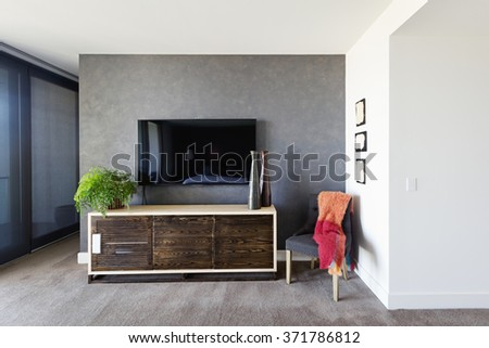 Wall Mounted Tv And Buffet In Spacious Master Bedroom With Decor Items