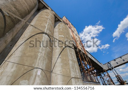 Wall of an old grain silo with the elevator in the distance - stock photo