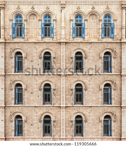 Wall of building from Jerusalem stone with blue shuttered windows - stock photo