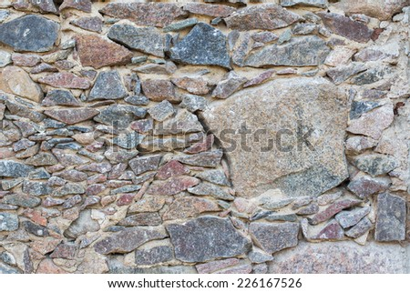 Wall of different stones - stock photo