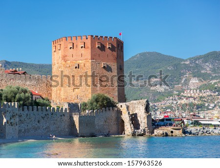 Wall of fortress and red tower in Alanya, Turkey  - stock photo