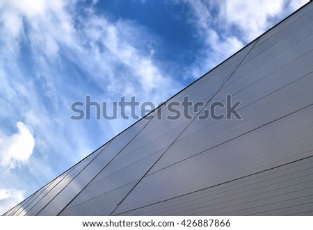 Wall of Industrial warehouse against a cloudy sky