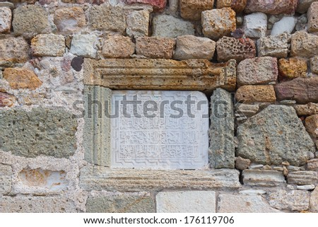 Wall of natural rough masonry. The city walls of Foca and Fife doors castle with Arabic inscription on marble table - stock photo