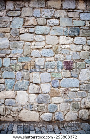 Wall of stones and pavement - stock photo