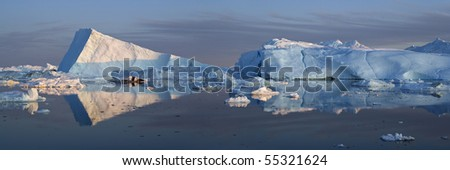 Wall of the Greenland ices and their reflexion in water - stock photo