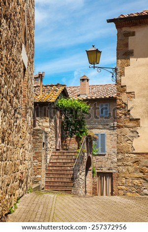 Wall of the old house and ladder in the ancient Italian town, Tuscany - stock photo